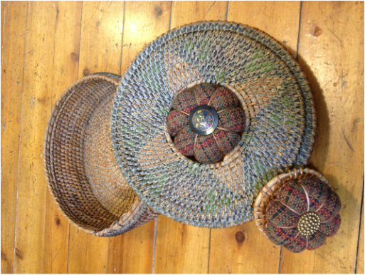 antique basket with handwoven pincushions